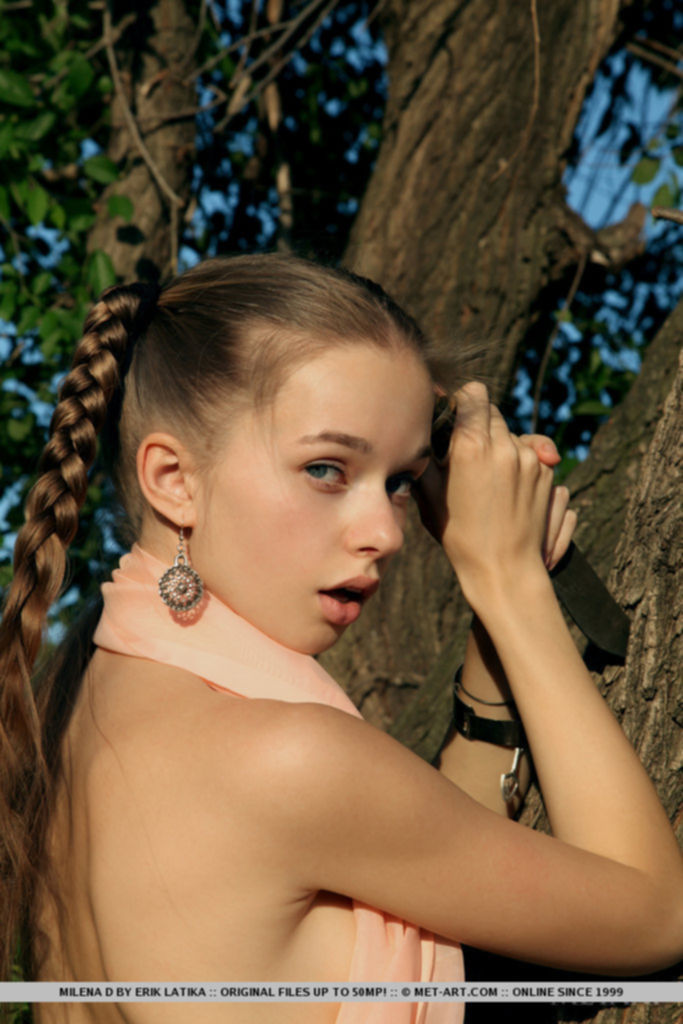 Красотка с милым лицом позирует голой у веревочной лестницы под деревом