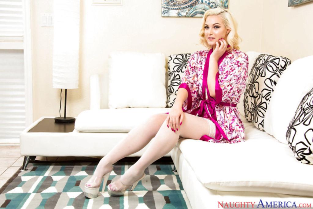 Белокурая красотка на высоких каблуках демонстрирует свое тело перед камерой